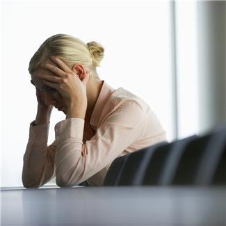 Stressad kvinna lutar huvudet i händerna